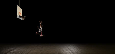 outdoor basketball court: Basketball court at night with lights on, basketball player jumping and aiming at hoop Stock Photo