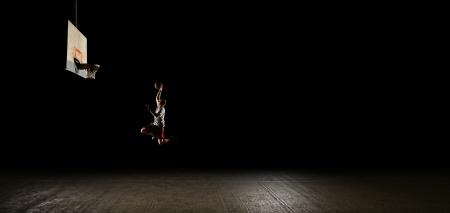 Terrain de basket dans la nuit avec des lumi�res sur, joueur de basket saut et visant � cerceau photo