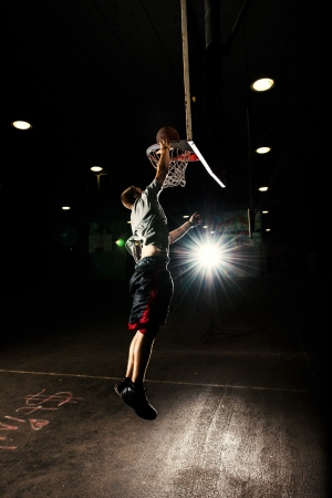Basketball court at night with lights on, basketball player jumping and throwing a basket