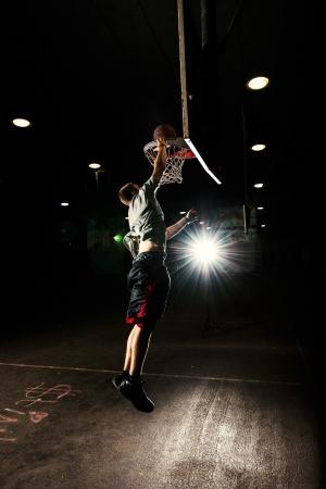 Terrain de basket dans la nuit avec des lumi�res sur, joueur de basket saut et de lancer un panier Banque d'images - 16717935