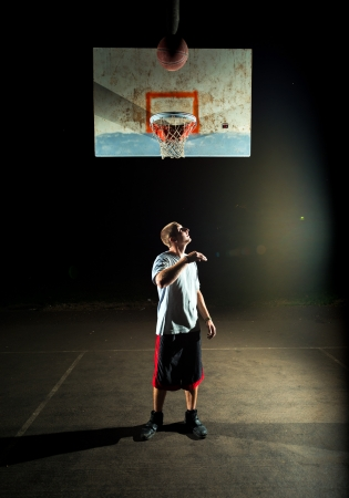 Basketball court at night with lights on, basketball player with his back to the hoop observing the ball photo