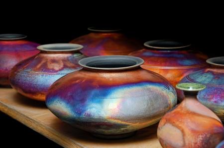 Rijen van iriserende glazen handgemaakt aardewerk en aardewerk op houten rekken in een winkel of winkel