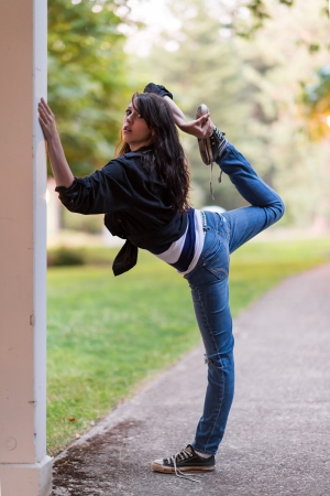 Young girl is stretching her leg, while holding on to a wall photo