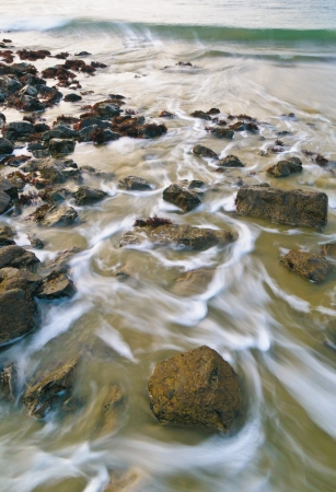 Closeup of a beautiful beach where water is washing over the rocks.