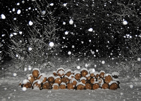 Stacked wooden logs in the snow with snowflakes at night