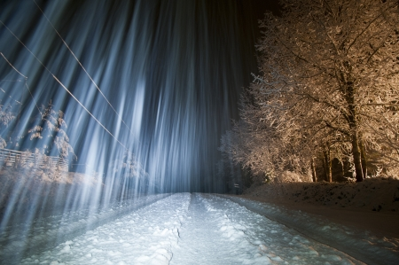 Winter trees and snow covered roadcovered in ice and snow with long camera exposure while snowing Stock Photo