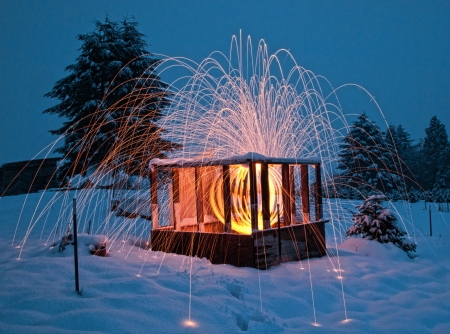happening: A beautiful photograph lighting and fireworks happening inside a wooden cabin with snow everywhere in the evening.