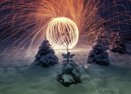 internships: Amazingly stunning display of colorful lighting works in the night on snowy landscape with Christmas trees around.