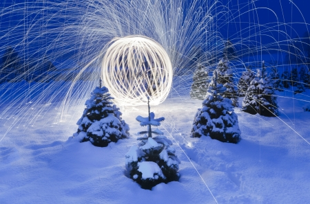 Image of beautiful lighting works display in a natural setting with lots of snow and Christmas trees around.