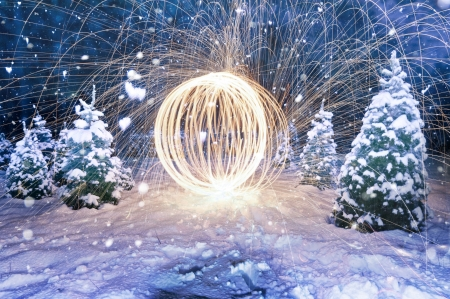 internships: Dramatic fiery sphere amongst snowy evergreen fir trees formed by light painting using burning steel wool revolving at the end of a line