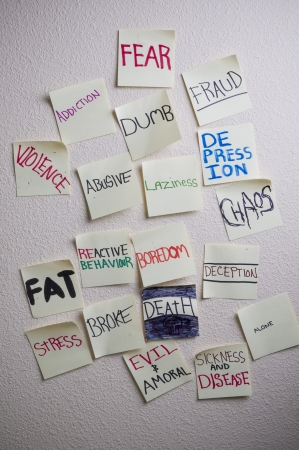 expressing artistic vision: Negative sticky notes on a white wall denoting Fear Addiction, Violence, Dumb, Abusive, Chaos, Fat, Boredom, Deception etc   Stock Photo