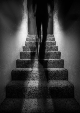 attic: Long exposure photograph of a a tall shadow figure walking up stairs. The image would work well with paranormal themes.  Stock Photo
