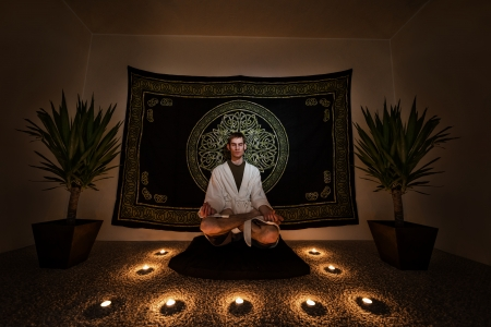magick: A man sitting on a zafu cushion with in a white robe with his eyes closed doing a  meditation ritual. There are plants, candles, and a tapestry behind him on the wall.