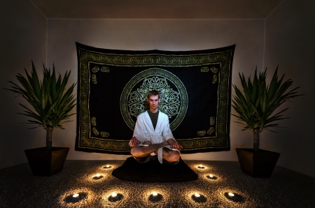 A man sitting on a zafu with in a white robe staring intensely into the camera with his eyes open doing a  meditation ritual. There are plants, candles, and a tapestry behind him on the wall.  photo