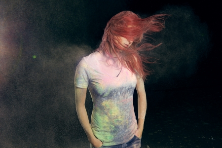 Redhead girl with colored powder trailing behind her hair that she is flinging up.  photo