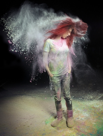 colored powder: Redhead girl with colored powder trailing behind her hair that she is flinging up.