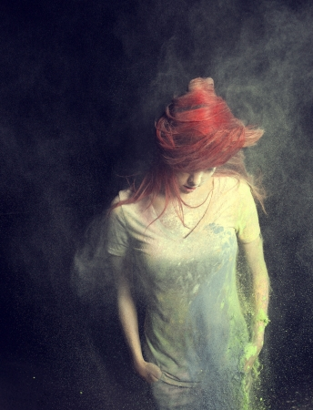 fling: Redhead girl with colored powder trailing behind her hair that she is flinging up.