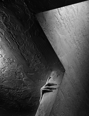fallacy: Photograph of a hand caught between a white wall and a black wall, symbolizing a dichotomy, dualism, pair, etc.