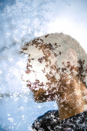 creates: A mans face staring and pondering in wonder as nature creates him.  Stock Photo