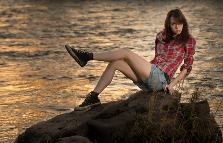 skiny: A young white caucasain female sitting on a rock near a river during sunset with her legs up. Stock Photo
