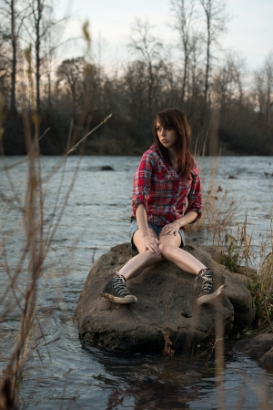 A young white caucasain female sitting on a rock near a river during sunset, staring out into the distance.