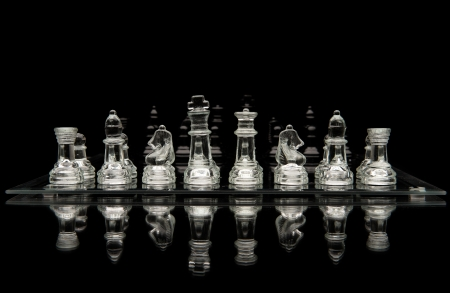 bishop chess piece: Glass Chess pieces on a glass chessboard with a reflection isolated on a black background