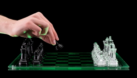 A hand makes the first move picking up a Glass pawn chess pieces on a glass chessboard with a reflection isolated on a black background photo