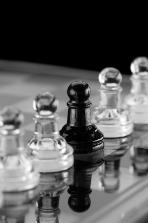 separatist: Glass Chess pieces on a glass chessboard with a reflection on a black background. Could be used as a concept for individuality. Stock Photo