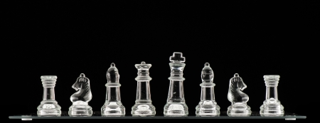 Clear glass chess pieces on a glass chessboard isolated on a black background photo