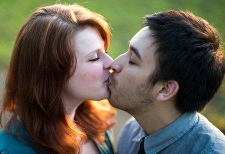 Amorous attractive young couple kissing outdoors backlit by the evening sun, head and shoulders portrait