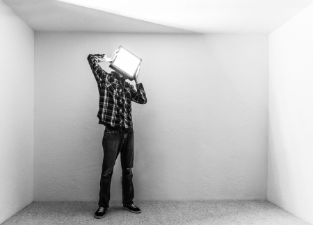 introvert: A man trapped in a small room with a square block with light coming out of it attached to his head.