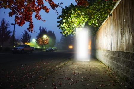Een deur naar een andere dimensie op een stoep naast een straat 's nachts de tijd met niemand rond. Stockfoto