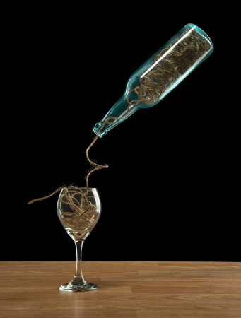 Wine bottle and glass filled with twine string over a black background