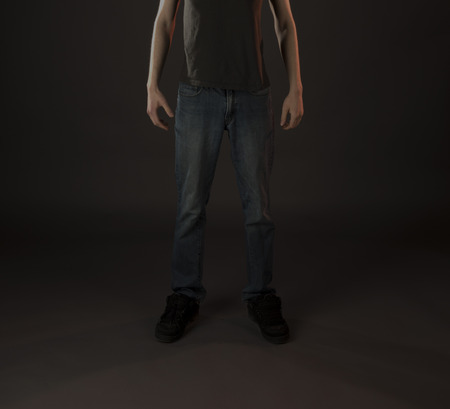 lower body: Man wearing black shoes and black shirt with dark blue jeans on a very dark backgroind. Stock Photo
