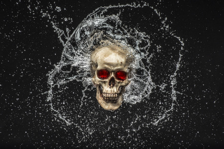 Skull with water splashing around it over a black background photo