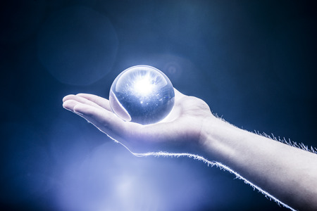 clairvoyance: Hand holding a clear transparent crystal glass ball in their palm