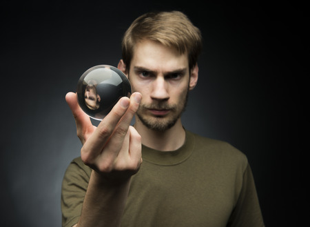 scrying: Young man holding a clear transparent crystal glass ball in their hand