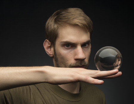 Young man holding a clear transparent crystal glass ball in their hand photo