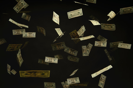 surfeit: US Dollar bills falling to the ground lit from above and isolated over a black background Stock Photo