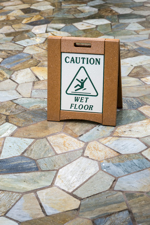 A sign on a slate tile floor that reads Caution Wet Floor photo