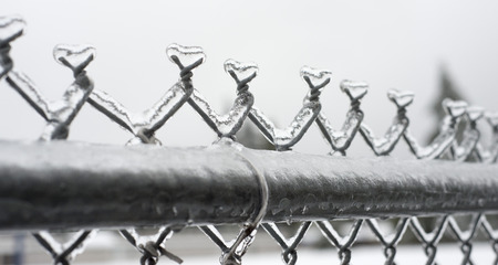 fencing wire: Close up of ice on top of a chain link fence Stock Photo