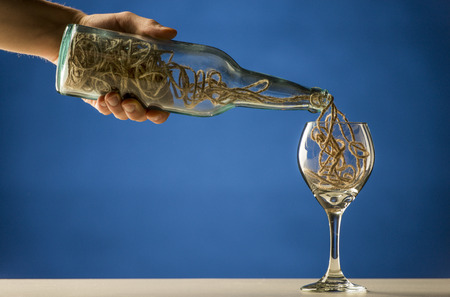 illogical: Man pouring a tangled mass of string from a transparent wine bottle into a wineglass in a conceptual image over blue with copyspace