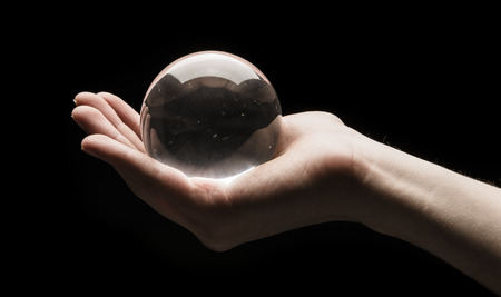 Hand holding a clear transparent crystal glass ball in their palm isolated on black background Stock Photo