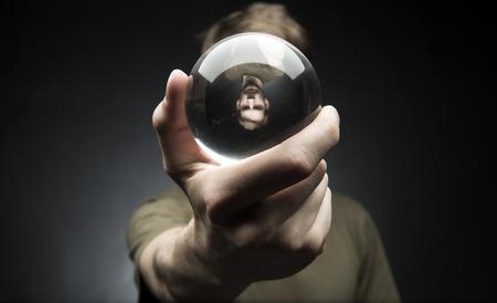 Jonge man met een helder transparant kristal glazen bol in hun hand