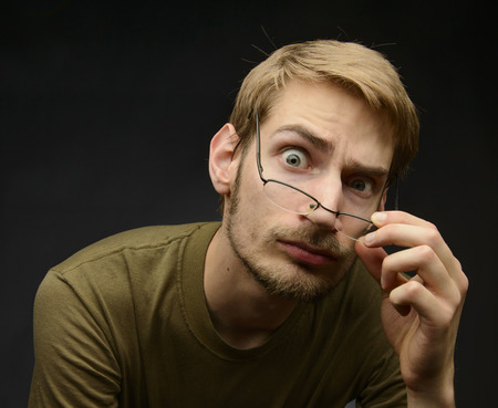 anal: Young man bringing down h is glasses to analyze and inspect something closely Stock Photo