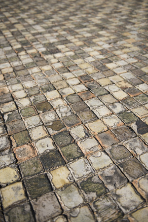 Very old and aged square tiles on the floor Stock Photo