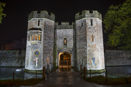wells: Bishops Palace Gatehouse in Wells, Somerset, UK illuminated at Night with the drawbridge out