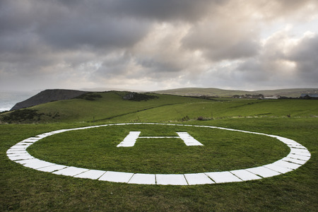helicopter pad: Helicopter landing pad in a grass field on the coast of Tintagel, Cornwall, UK