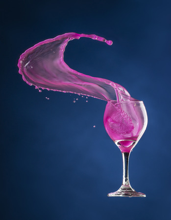 High speed studio photograph of pink liquid flying out of a wineglass in mid-air