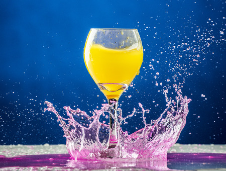 Yellow liquid in a wine glass fall onto pink liquid splashing on a table